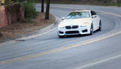 BMW Driving fast through Los Angeles hills pan Stock Footage