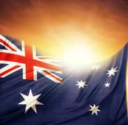 australian flag in front of bright sky - stock photo