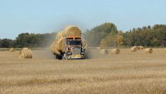 Truck loaded with hay bales crossing a field. Manitoba, Canada. Stock Footage
