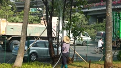 A middle-aged woman is giving tree watering, in Shenzhen's green belt Stock Footage