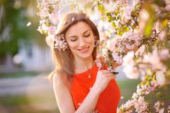 young woman in red dress standing among blossom trees - stock photo
