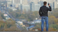 Man stand and phone at the high  altitude point of view by the city landscape Stock Footage