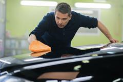 Man worker polishing car on a car wash Stock Photos