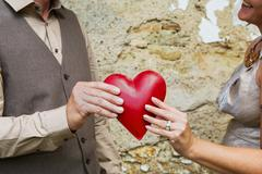 Valentine's day: couple holding red heart in her hands. Stock Photos