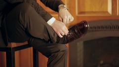 Distinguished man ties his shoes - medium shot Stock Footage