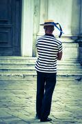 gondolier on the docks awaiting tourists in venice, italy - stock photo
