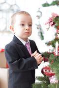 Boy decorate a christmas tree for christmas Stock Photos