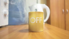 "Turning the mug on the table from ""off"" text to ""on"" Stock Footage"