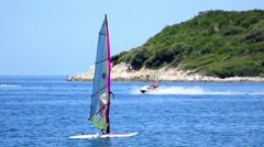 Windsurfer riding the waves near island rocky coast Stock Footage