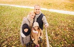 Happy family with selfie stick in autumn park Stock Photos