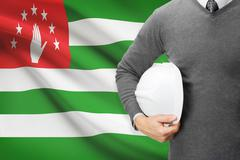 engineer with flag on background  - abkhazia - stock photo