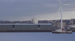 4k wind turbine at industrial sea front, Liverpool docks with the Mersey ferry Stock Footage