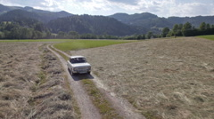 Aerial, front view - Old, white car driving on a field road Stock Footage
