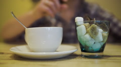 Woman putting sugar into tea cup using tongs Stock Footage