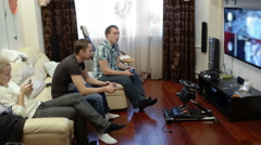 Men playing video game and girl using cell phone Stock Footage