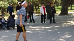 Man playing a shuttlecock in a park in Shanghai, China Stock Footage