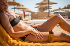 Sensuous slim woman applying suntan oil - stock photo