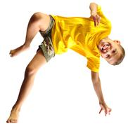 Cute boy exercising, dancing and jumping over white Stock Photos
