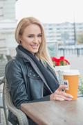 Attractive woman sitting drinking coffee - stock photo