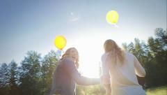 Girls Walk With Balloons, One Trips, The Other Tries To Help, They Both Laugh Stock Footage