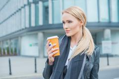 Attractive blond woman standing drinking coffee - stock photo