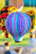 bunch of hot air balloon toys dangling in the wind - stock photo