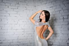 Beautiful luxury woman model posing in dress with open back. fashion evening  Stock Photos