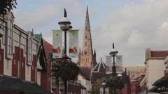 The Spire of Lichfield Cathedral Towering above Roof of Shopping Mall Stock Footage