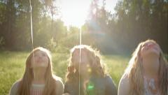 Camera Pans From Balloons Down To 3 Sisters, They Look Up At Balloons Stock Footage