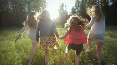 Sisters Hold Hands And Run Through A Field (Slow Motion) One Trips And Falls - stock footage