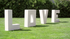 large letters LOVE on the grass - stock footage