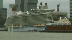 Cruise ship moored at cruise terminal, container vessel passing + zoom out Stock Footage