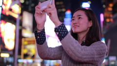 Stock Video Footage of Young Asian Woman in city at night taking a selfie photo picture
