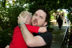 Loving father comforts fussing son Stock Photos