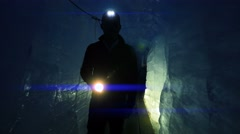 Silhouette of scientist researcher discovering glacier cave holding flashlight Stock Footage