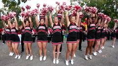 Large group of college cheerleaders dancing to the beat with pom poms - stock footage