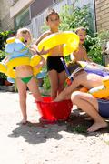 four little children splashing and having fun in their yard - stock photo