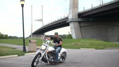 Cool shot of bridge with biker getting on motorcycle and riding away Stock Footage