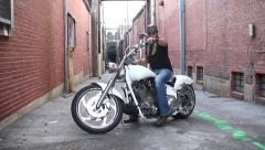 Cool rocker dude getting on bike in alley and riding off Stock Footage