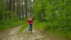 Happy kid running along the road in a summer forest Stock Footage