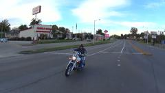 Motorcycle front view as it turns at intersection Stock Footage