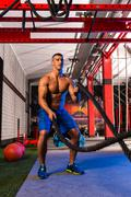 Battling ropes man at gym workout exercise Stock Photos