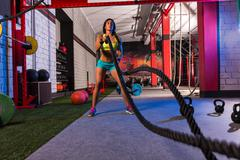 Battling ropes girl at gym workout exercise Stock Photos