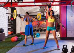 barbell weight lifting man woman rising kettlebell - stock photo