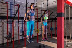 gym girls muscle ups rings gym workout - stock photo