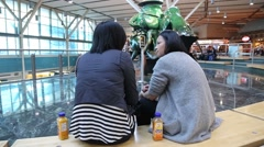 One side of airport terminal with two friends take a rest in waiting area . Stock Footage