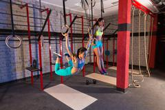 gym girls muscle ups rings swinging workout - stock photo