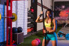 Beautiful fitted girl at gym with black rope Stock Photos