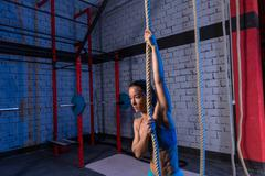 Climb rope exercise woman at gym Stock Photos