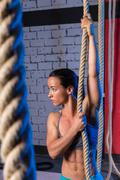 climb rope exercise woman at gym - stock photo